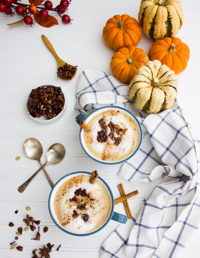 2 bowls of pumpkin spice oatmeal latte on a table with a table cloth and two spoons and some pumpkins