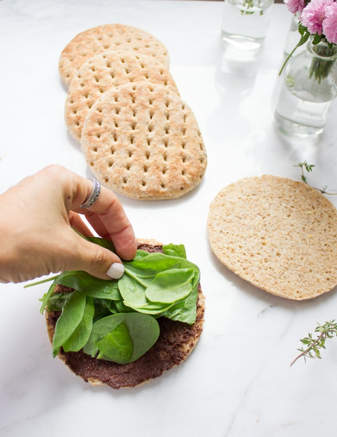 A hand piling up some fresh spinach leaves over the tapenade spread pita bread bun