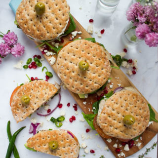 Top view of a white granite with a wooden board and turkey sandwiches over the wooden board. Another cut sandwich on the sandwich and flowers. Green chillies next to the cut up sandwich.