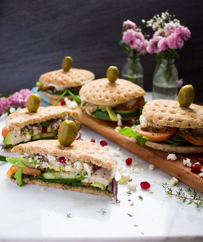 A cut up turkey sandwich on a white granite surface with the remaining turkey sandwiches behind it showing faintly. A green olive is skewered over every sandwich top. Some feta cheese is crumbled around it.