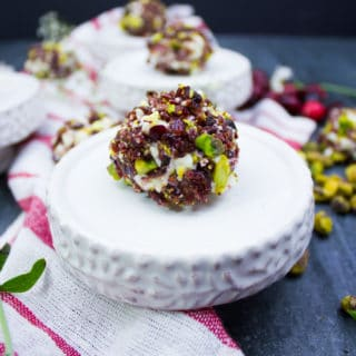 A single mini cheesecake coated in cranberries and pistachios over a small serving plate. A tea towel is around it with scattered pistachios.