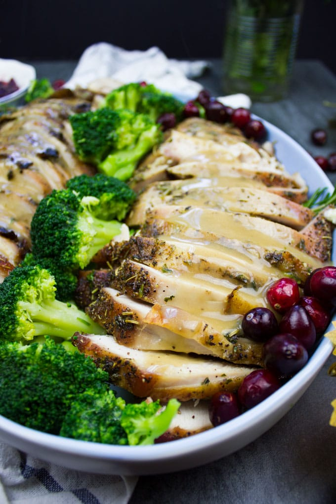Close up of the finished sliced turkey breasts on a platter with some broccoli and fresh cranberries