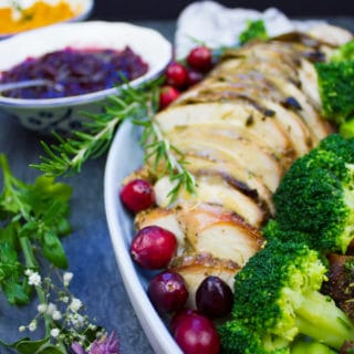 A platter showing close up of some slices of roast turkey, a flower and some broccoli