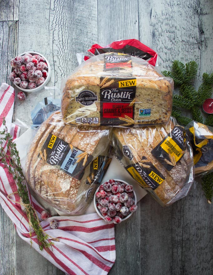 3 bags of The Rustik Oven Breads over a wooden table and a red tea towel with a bowl of frosted cranberries on the side