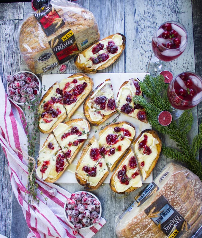 Top view of all the finished baked brie toasts on a white marble over a wooden table with bags of bread around it, some cranberry cocktails and frosted cranberries
