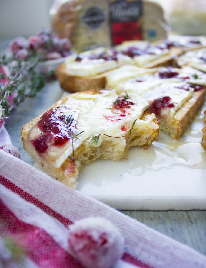 A bitten piece of baked brie toast with cranberry sauce over a white marble
