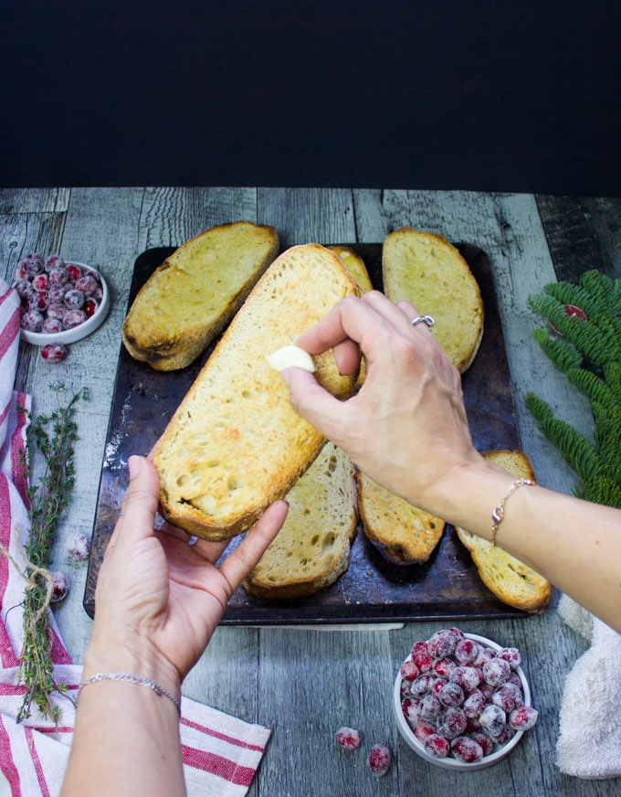 Two hands holding a piece of toasted bread and rubbing in a garlic clove into the bread for flavor