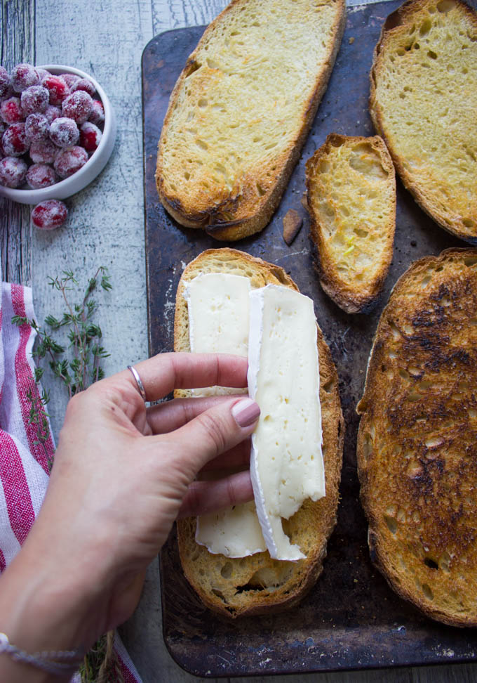 A hand placing slices of brie cheese over toasted bread on a metal sheet pan