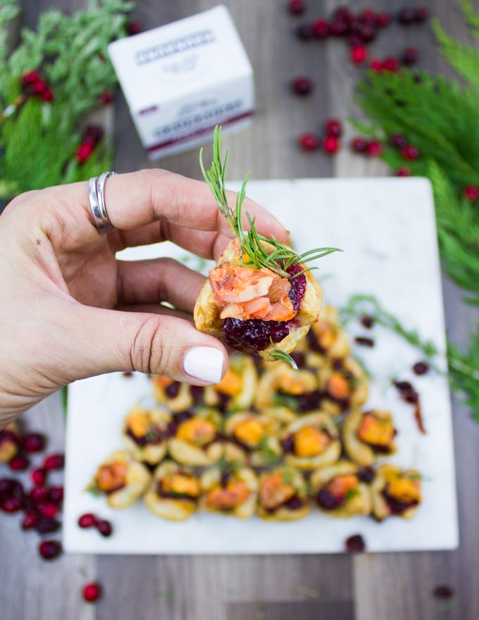A hand holding a full piece of the easy appetizer stuffed with cranberry sauce, cheese and a rosemary sprig close up.