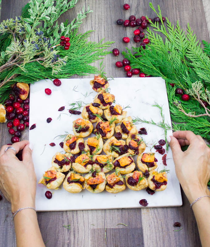 A hand serving a marble of a fully loaded easy appetizer festive tree shaped pastries for a party or a crowd.