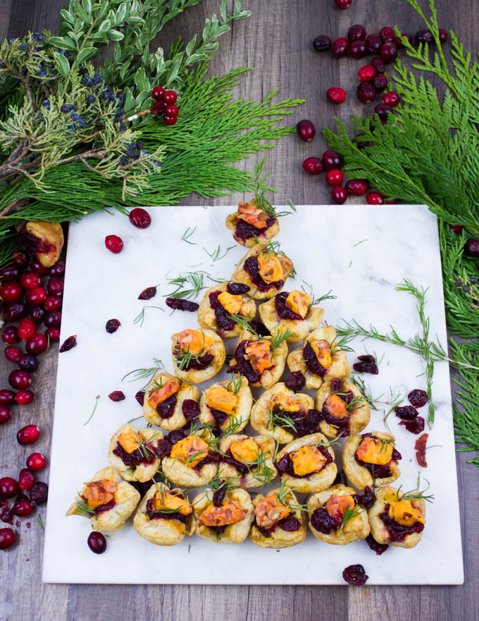A tree shaped easy appetizer of mini pastries on a white marble board surrounded by fresh cranberries and green wreath leaves.