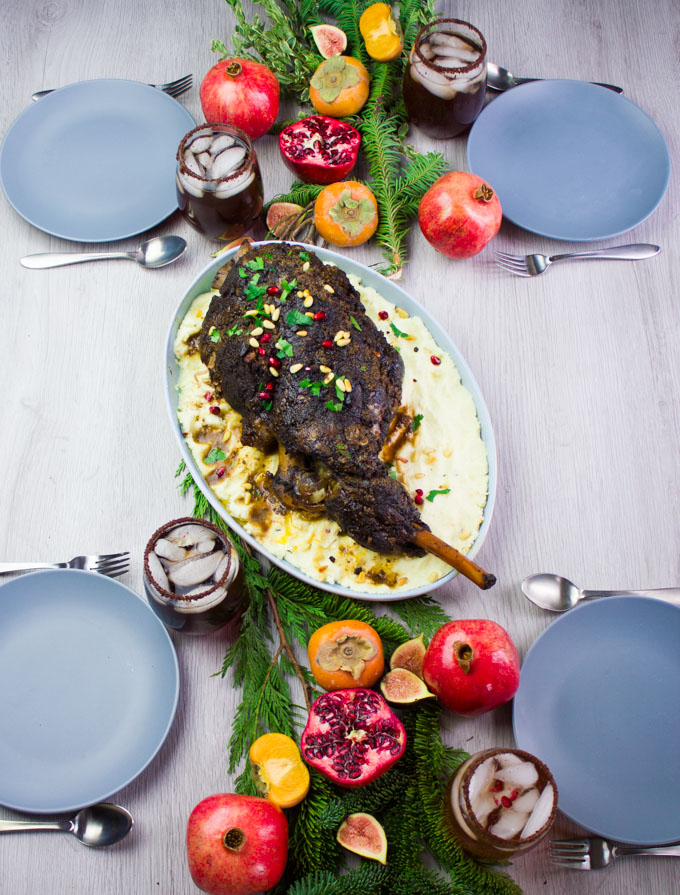 A table with four plates and drinks and a main dish of leg of lamb with mashed potatoes in the middle surrounded by pomegranates and greens