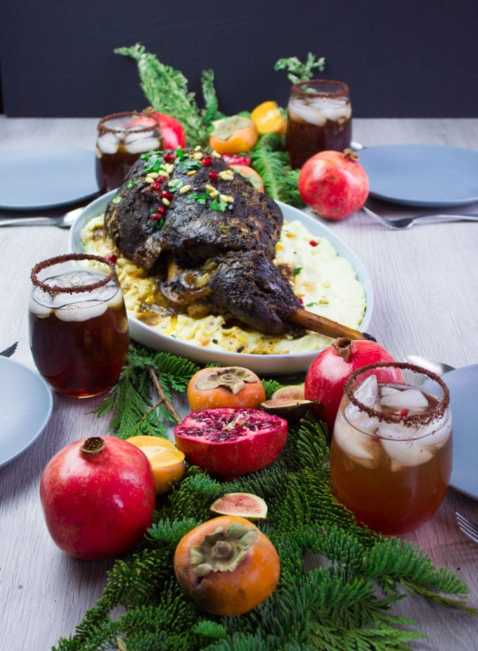 A few cups with drinks on a table and a few winter greens and fruits surrounding a big plate of a whole leg of lamb recipe served with mashed potatoes under.