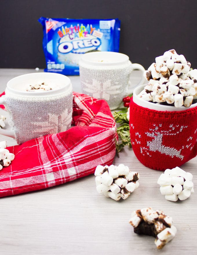 A side view of the mug holding several OREO cookie balls, and an OREO pack at the background and two hot chocolate cups at the back.
