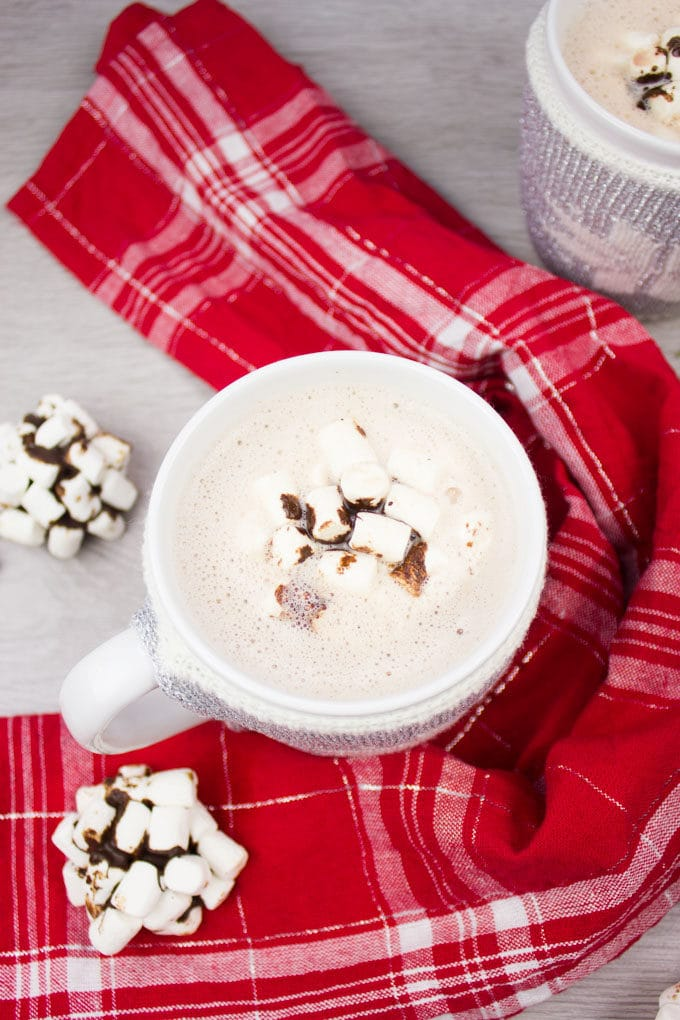A single cup of hot chocolate surrounded by a red towel and topped with OREO cookie balls.