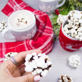 A hand Holding an OREO cookie balls coated in marshmallows up close, with two hot chocolate drinks at the back.