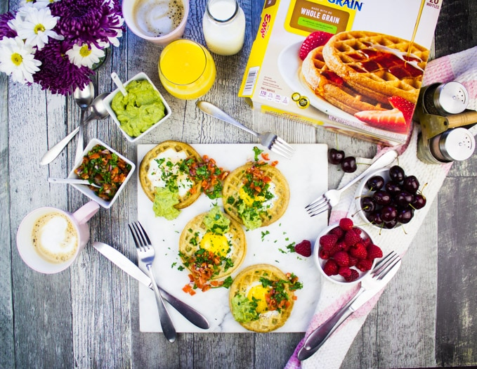 Top view of a breakfast table with egg in a hole wafles topped with guacamole and salsa, a box of waffles, some coffee, orange juice and berries to eat.