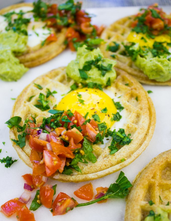 Single egg in a hole waffle up close with pico de gallo and guacamole on top.