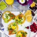 Finished breakfast table with four egg in a hole waffles, some flowers and berries, extra guacamole and jam on the side.