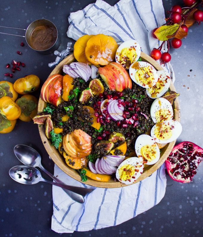 A top view of a kale salad bowl with fruits, hard boiled eggs, spicy lentils surrounded by fresh fruits, a kitchen towel and some spoons.