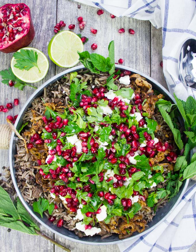 A top view of a plate of lentils and rice cooked mujadara recipe with crispy fried onions and herbs