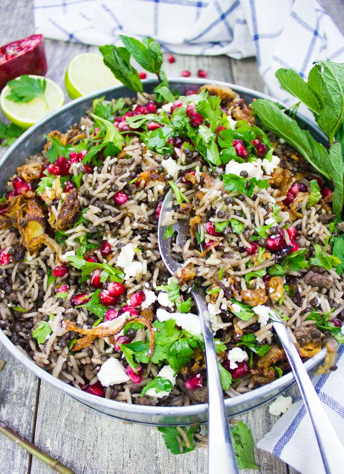 A plate of cooked Mediterranean rice and lentils aka mujadara with two spoons serving up the dish showing crispy onions and herbs on top