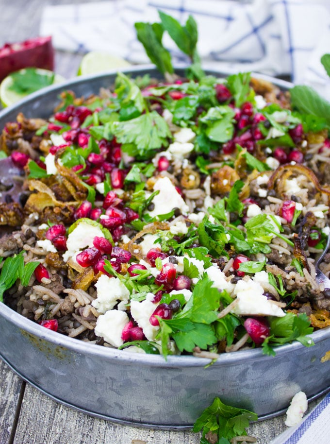 Side view of a plate of mujadara showing close up of the cooked rice and lentils and some feta cheese crumbles on top with lots of fresh herbs