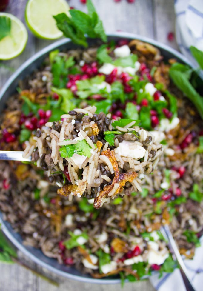 A spoon holding some mujadara cooked showing the detailed crispy onions, cooked rice and lentils with herbs and pomegranate arils on top
