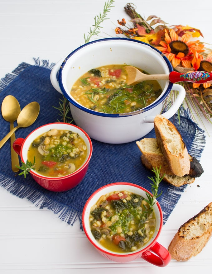 A pot of white bean soup recipe and two bowls of soups, two spoons and some crunchy bread.