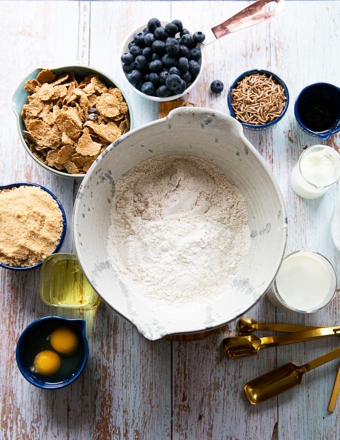 ingredients for the bran muffins including flour, baking powder, baking soda, bran, brown sugar, eggs, oil, vanilla, milk