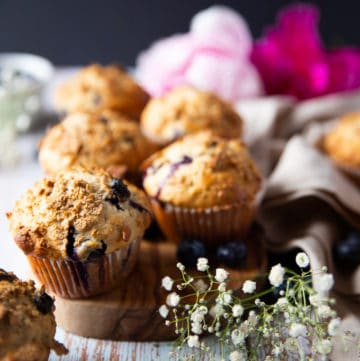 A bran muffin over a wooden board with more bran muffins at the back surrounded by small white flowers