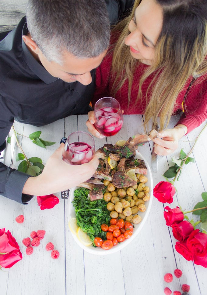 Two people lookig at each other and enjoying the lamb platter together for Valentine's Day. One of them holding a lamb chop while the other holding the drink.