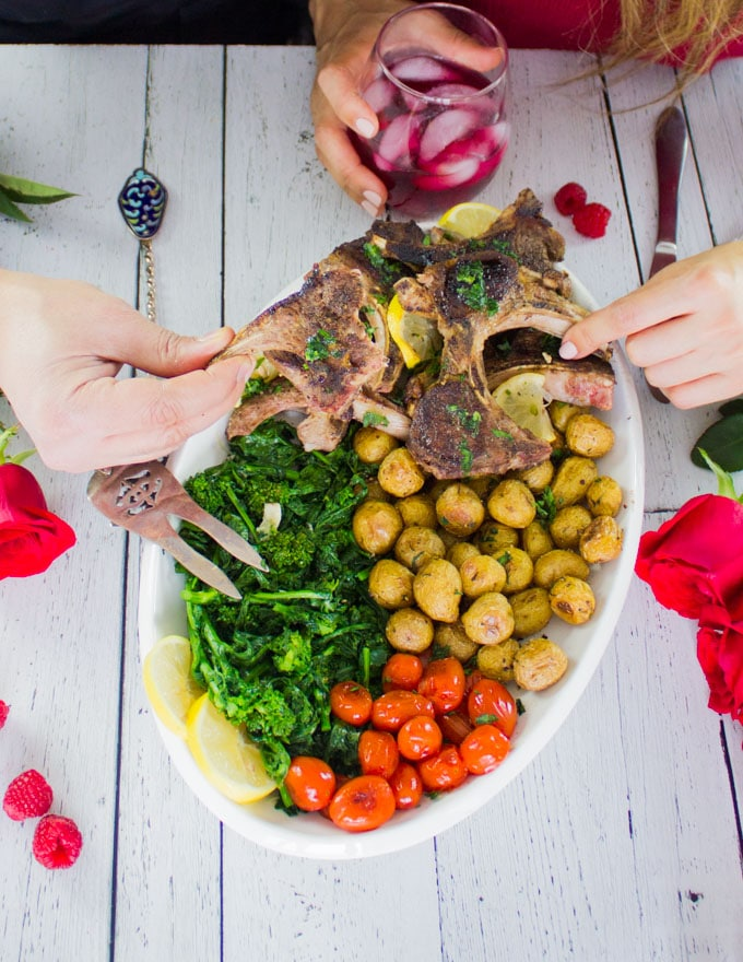two hands holding a lamb chop each over the lamb chops platter with potatoes, broccoli, and tomatoes.