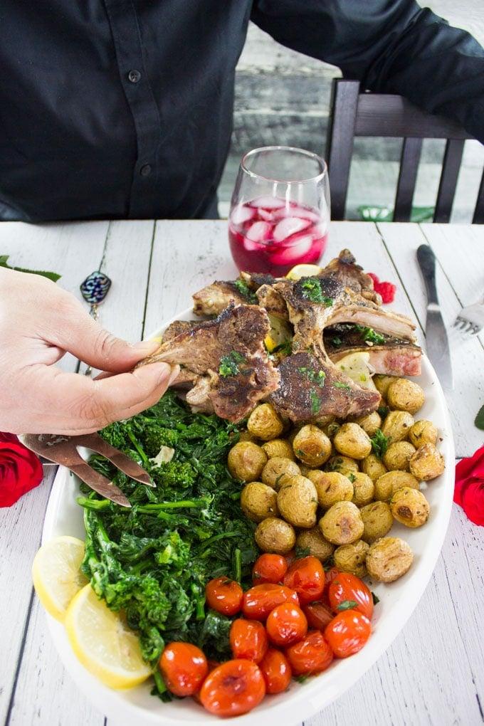 A hand holding a bitten piece of lamb chops showing the succulent lamb