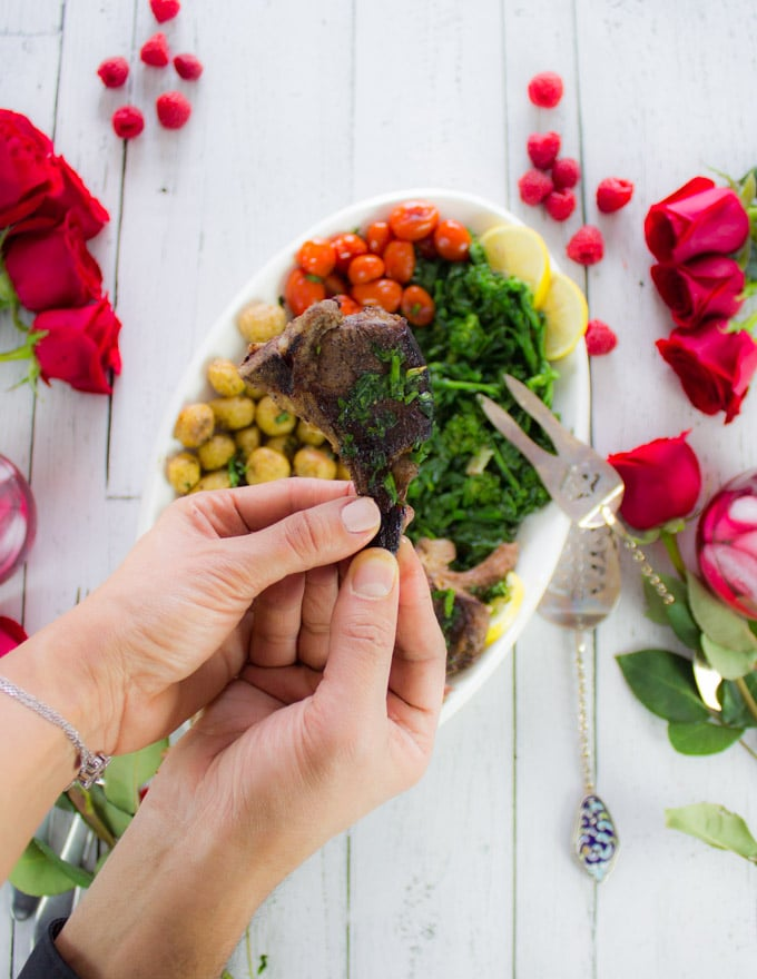 two hands sharing and holding a single lamb chop over a platter of lamb chops and roses, raspberries and drinks for a date night table set up
