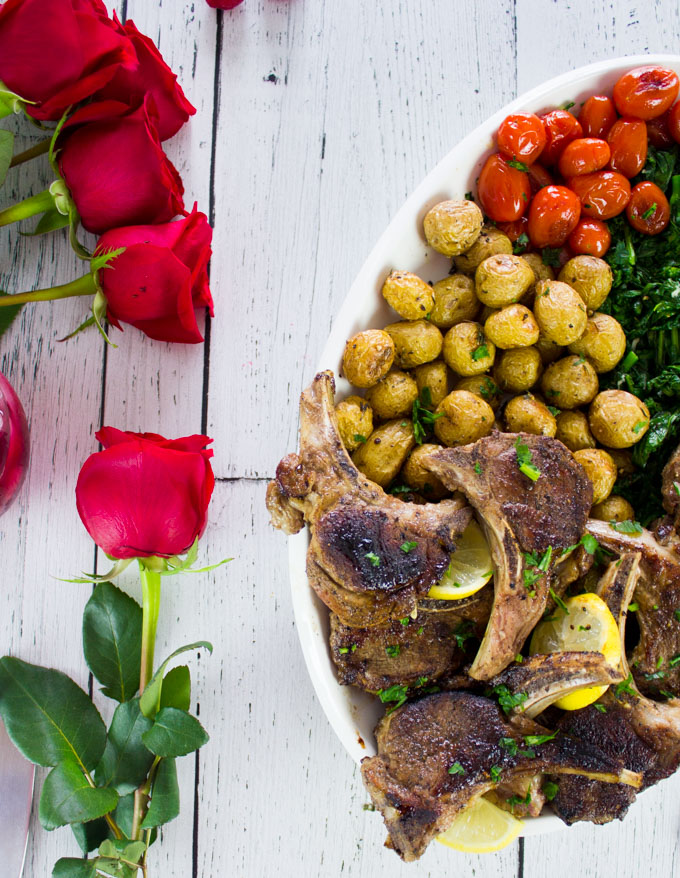 Half a platter of lamb chops on a white table with red roses
