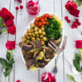A full platter of lamb chops, roast potatoes, garlic broccolini and tomatoes, surrounded by red roses and drinks