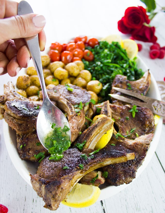A spoon drizzling some compound herb butter over cooked lamb chops