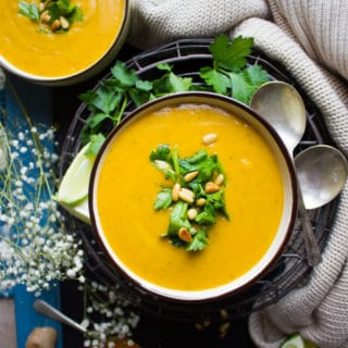 A bowl of butternut squash recipe surrounded by two spoons, some lime and cilantro.