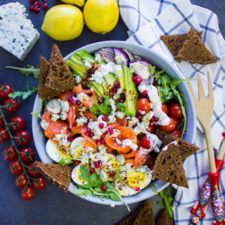 A huge bowl os smoked salmon salad with pumpernickel croutons, surrounded by a tea towel, some fresh lemons and two salad spoons.
