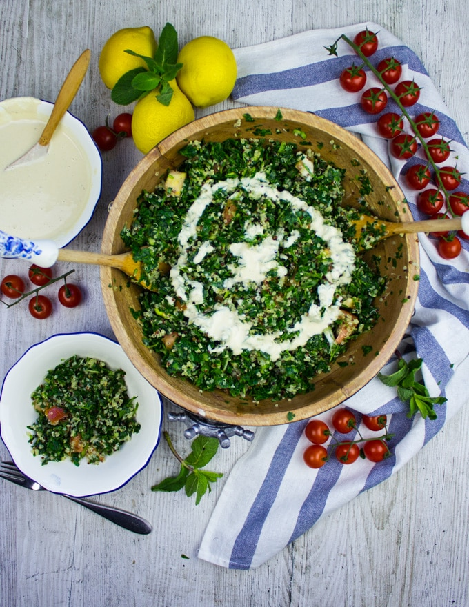 Finished tabouli salad with two serving spoons and a small plate of salad on the side