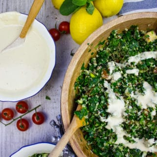 A half a bowl of tabouleh salad with lemons on a table and a bowl of tahini dressing