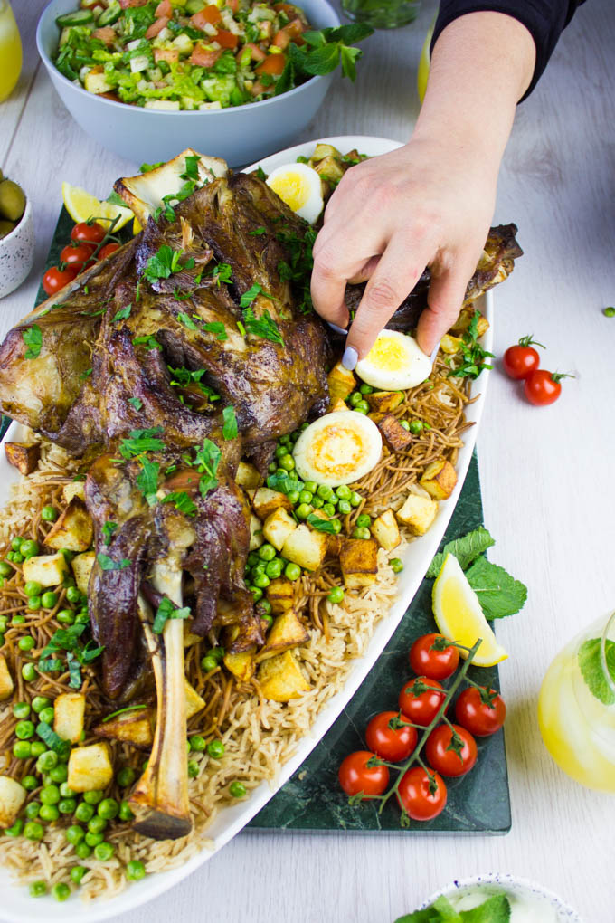 A hand arranging the hard boiled eggs on the rice all around the lamb shoulder.