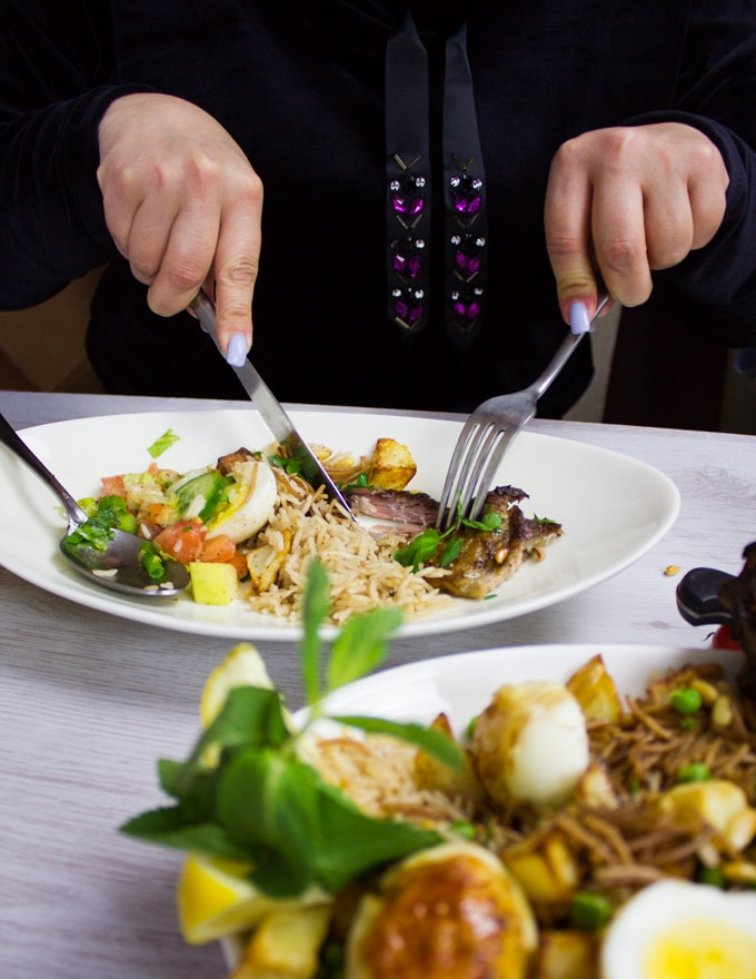 A plate with a bit of lamb shoulder, some rice and salad and a hand holding fork and knife eating and enjoying the meal
