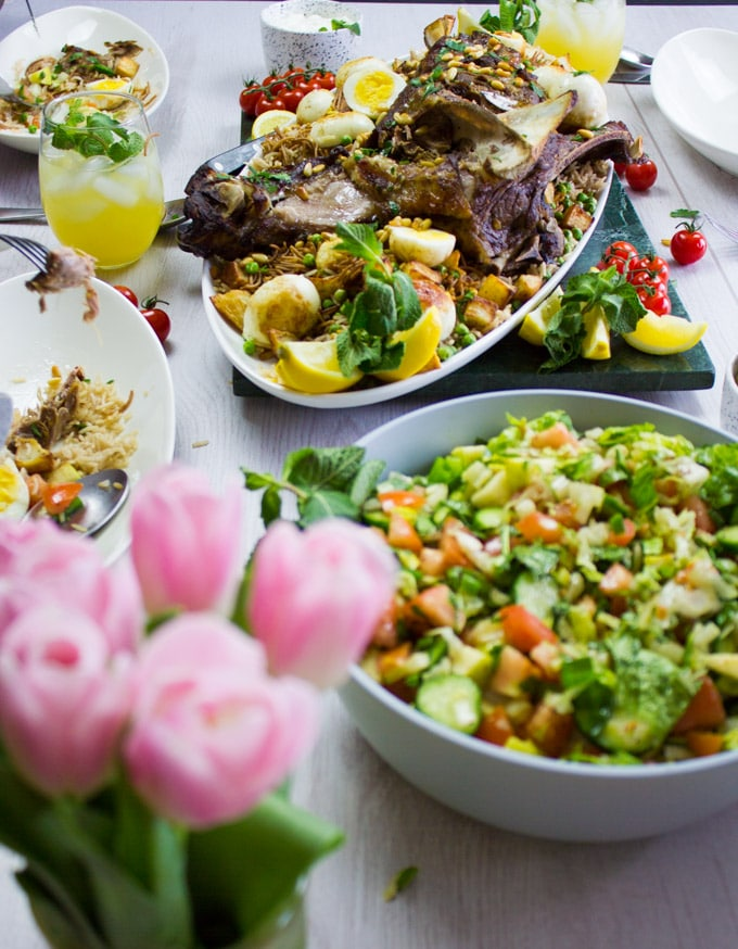 A table set up with flowers, salad and the roast lamb shoulder eaten up and enjoyed.