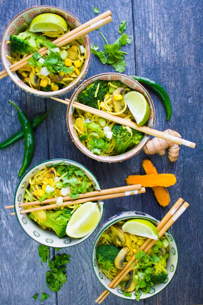 A set of 4 spicy ramn bowls with chopsticks and green chillies, lime wedges and turmeric root around it.