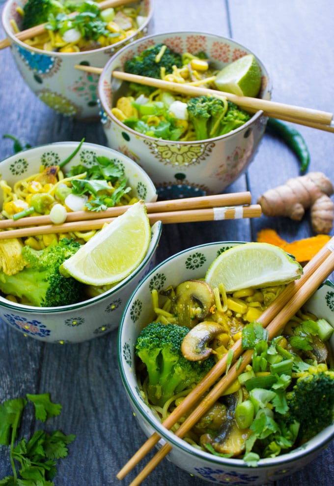 3 spicy ramen bowls with chopsticks and lime wedges, broccoli and mushrooms