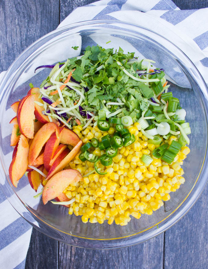 A big bowl of fish taco slaw ingredients including corn kernels, sliced peaches, broccoli slaw, jalapenos, scallions, cilantro