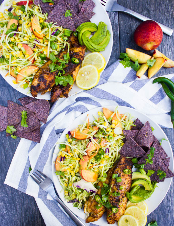 two plates of fish taco recipe with a tea towel in the middle, a peach, some green chillies, some blue corn, lemon slices