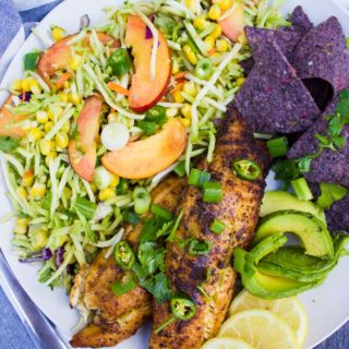 A close up of the fish taco recipe showing the taco slaw with peaches, a sliced avocado and lemon slices